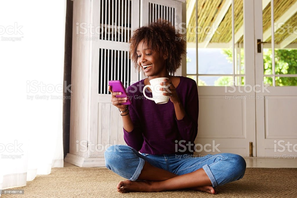 Smiling woman sitting on floor at home with cell phone stock photo