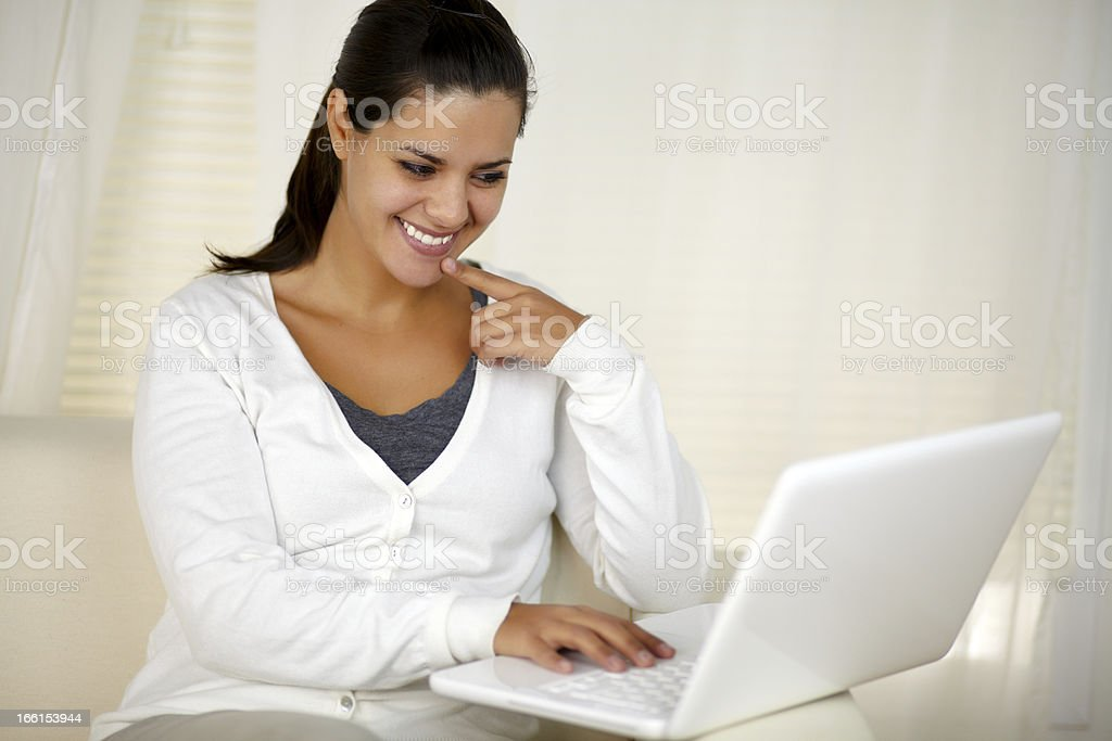 Smiling woman sitting on sofa using her laptop royalty-free stock photo