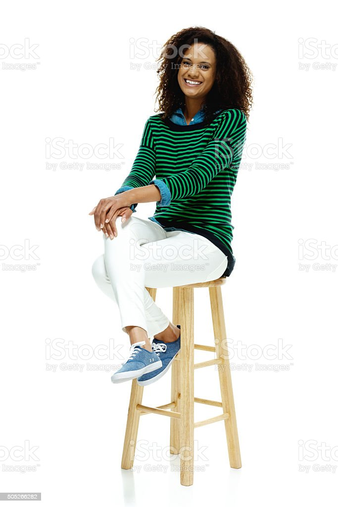 Smiling woman sitting on stool stock photo