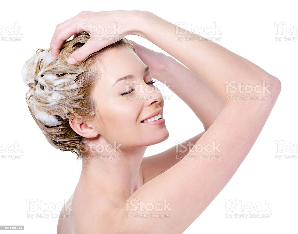 Smiling woman soaping her hair stock photo