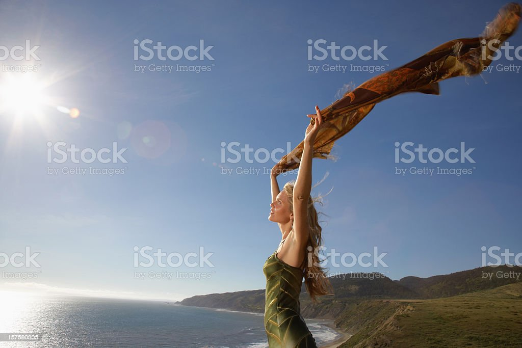 Smiling Woman Standing Above Ocean With Outstretched Scarf royalty-free stock photo