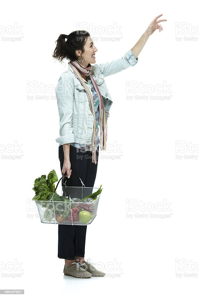 Smiling woman standing and holding basket royalty-free stock photo