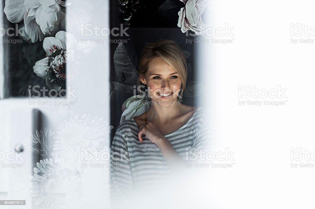 Smiling woman standing at doorway in backyard stock photo