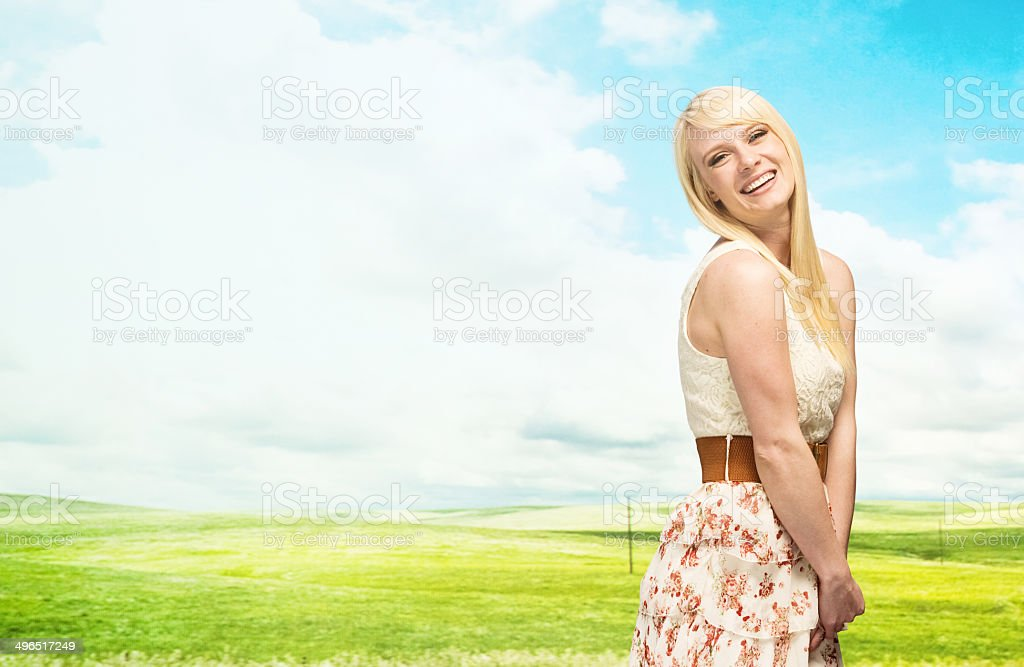 Smiling woman standing in front of rural scene royalty-free stock photo