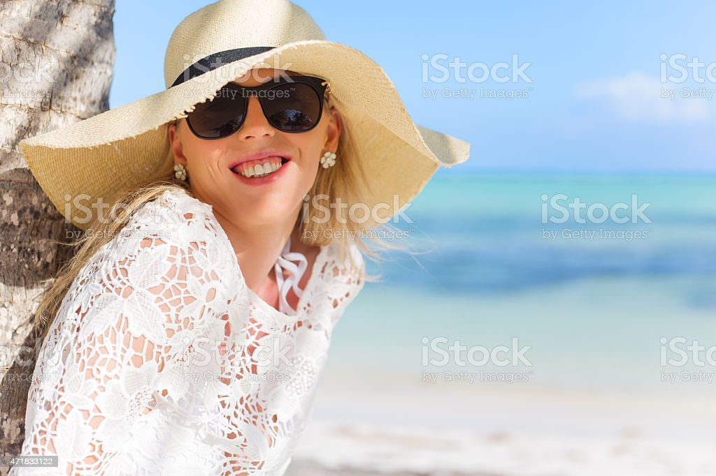 Smiling woman standing under palm tree stock photo