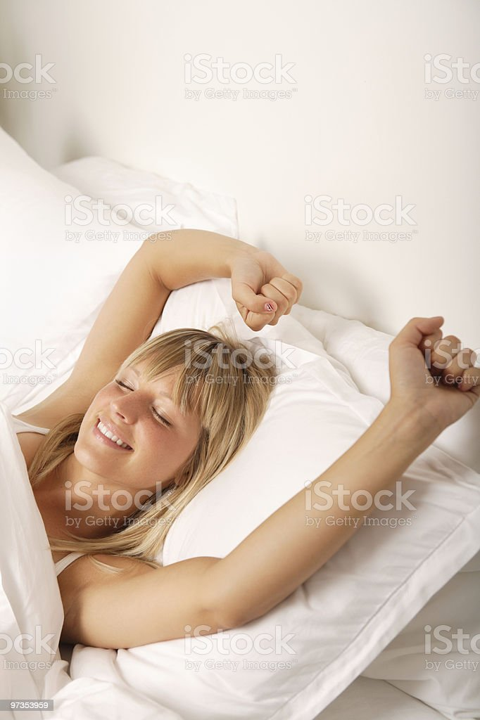 Smiling woman stretching in bed royalty-free stock photo