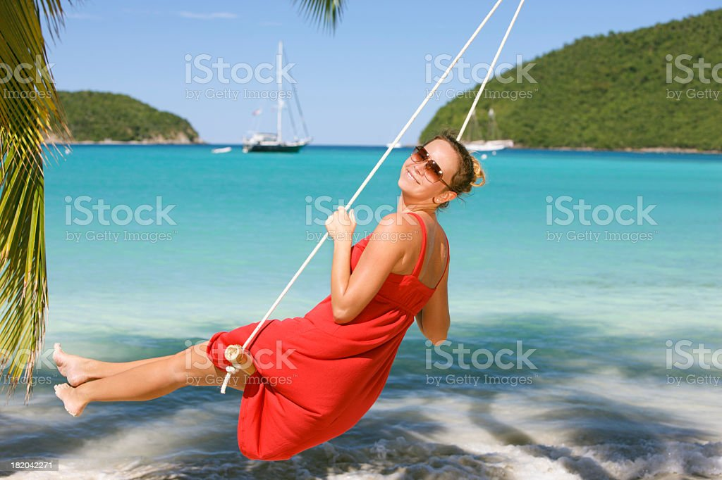 smiling woman swinging at a beach in the Caribbean stock photo