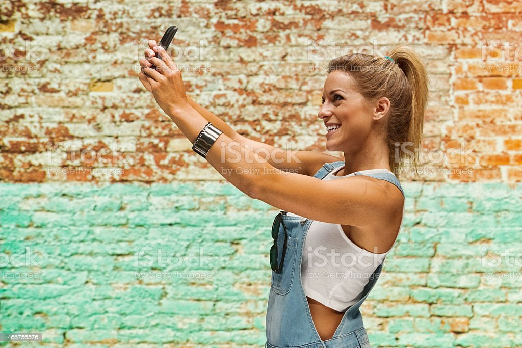 Smiling woman taking a selfie in front of brick wall stock photo