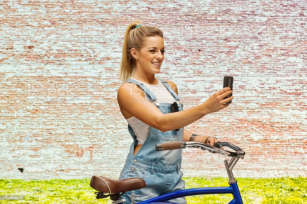 Smiling woman taking a selfie outdoors stock photo