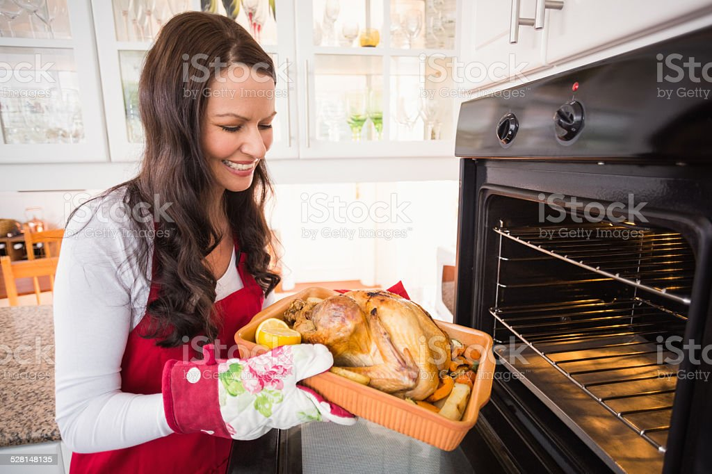 Smiling woman taking out her roast turkey stock photo