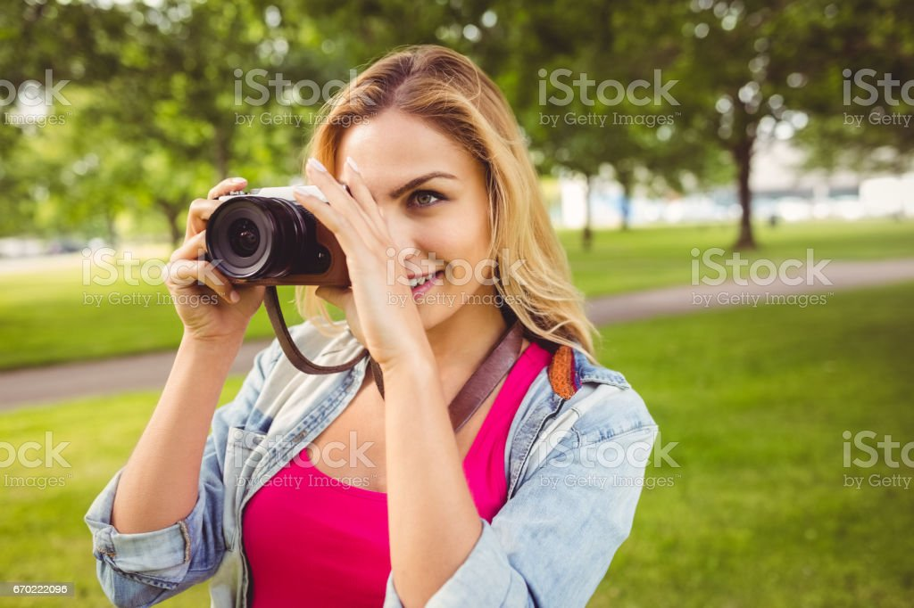 Smiling woman taking picture with camera stock photo