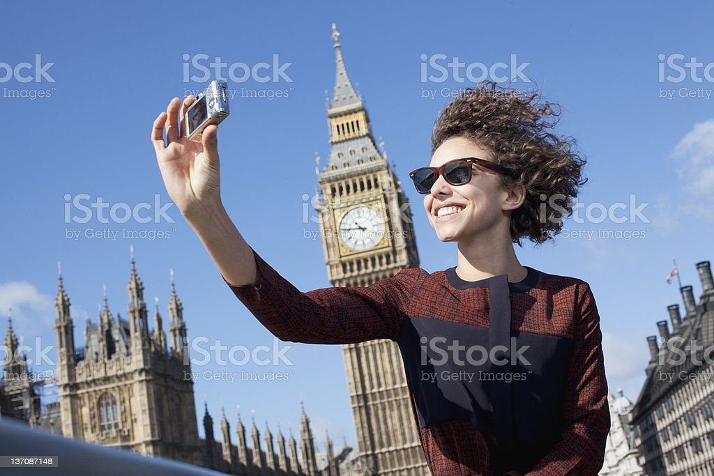 Smiling woman taking self-portrait with digital camera below Big Ben clocktower royalty-free stock photo