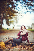 Smiling woman talking on the phone during autumn day