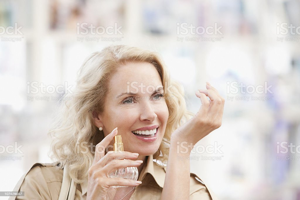 Smiling woman testing perfume in store royalty-free stock photo