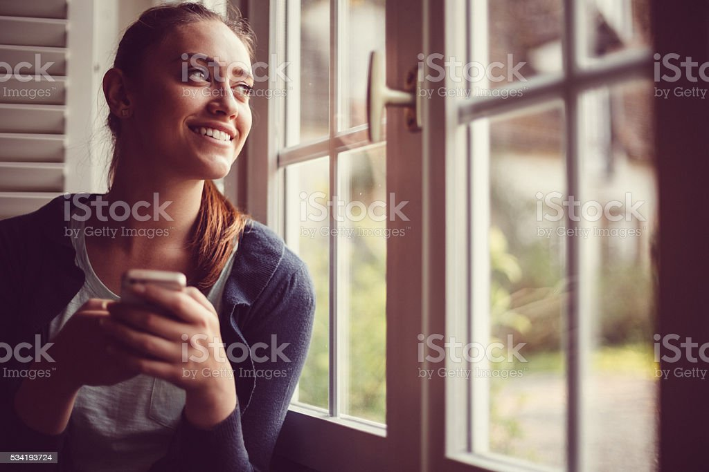 Smiling woman texting and looking through the window stock photo