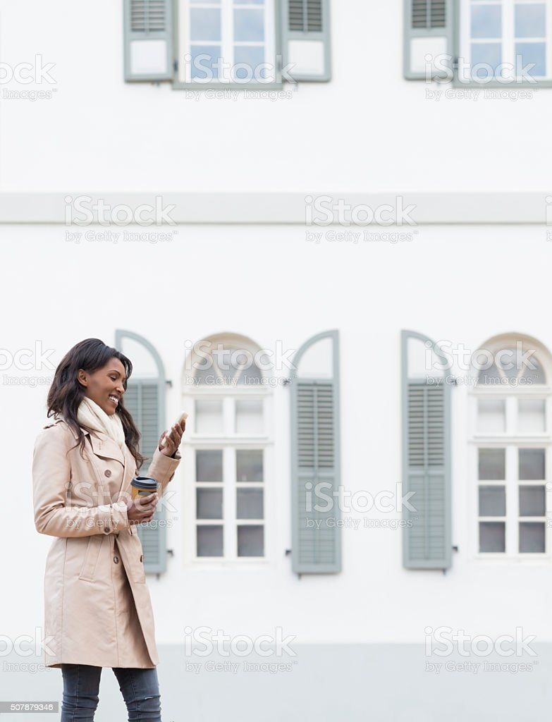 Smiling woman texting on her cell phone. stock photo