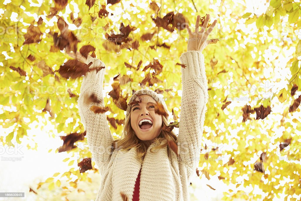 Smiling woman throwing autumn leaves in the air on sunny day royalty-free stock photo