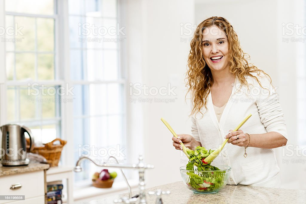 Smiling woman tossing salad in kitchen royalty-free stock photo