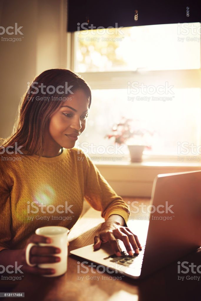 Smiling woman typing on laptop near sunny window stock photo