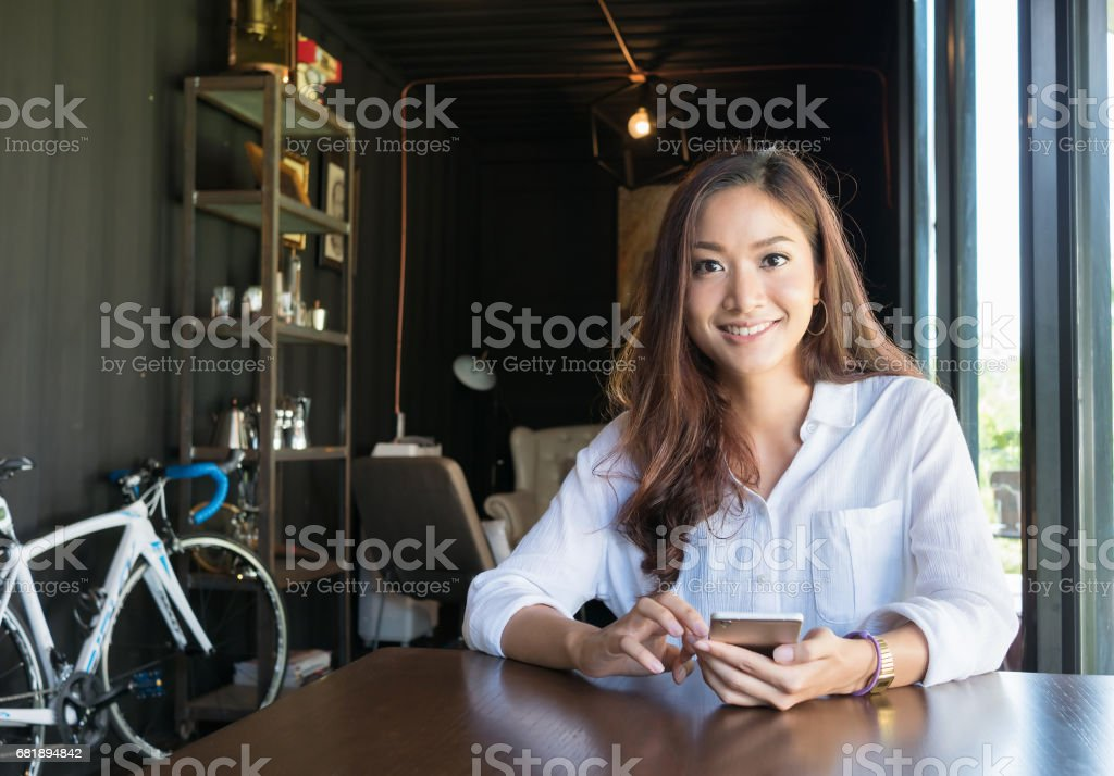 smiling woman typing text massage in smart phone stock photo