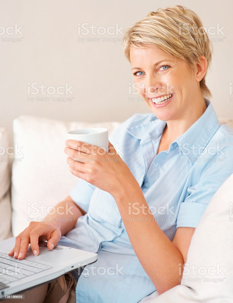 Smiling woman using a laptop and holding coffee royalty-free stock photo