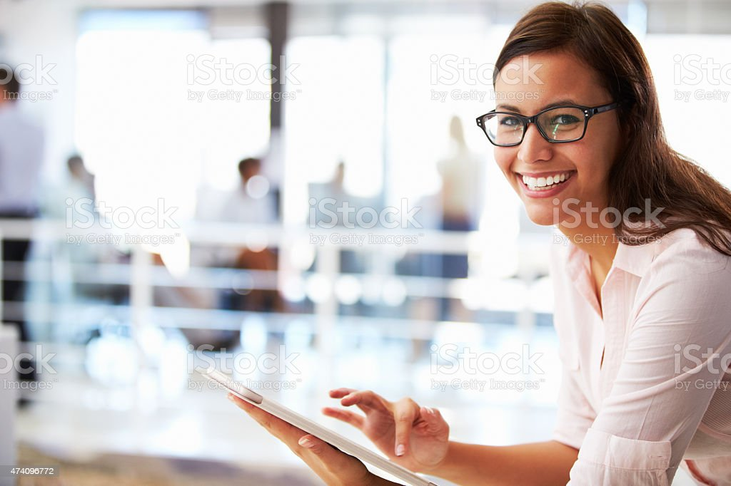 Smiling woman using a tablet in an open office setting stock photo