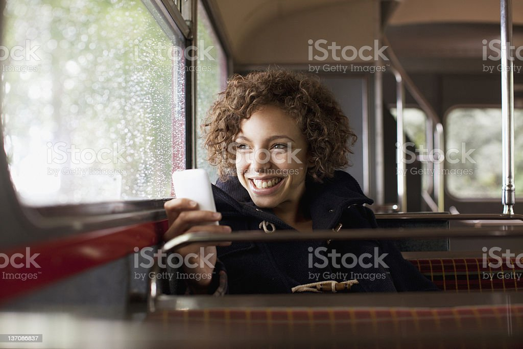 Smiling woman using cell phone on bus stock photo
