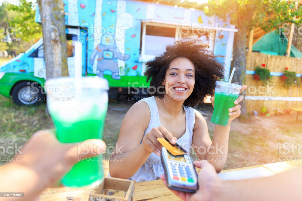 Smiling woman using credit card outdoors stock photo