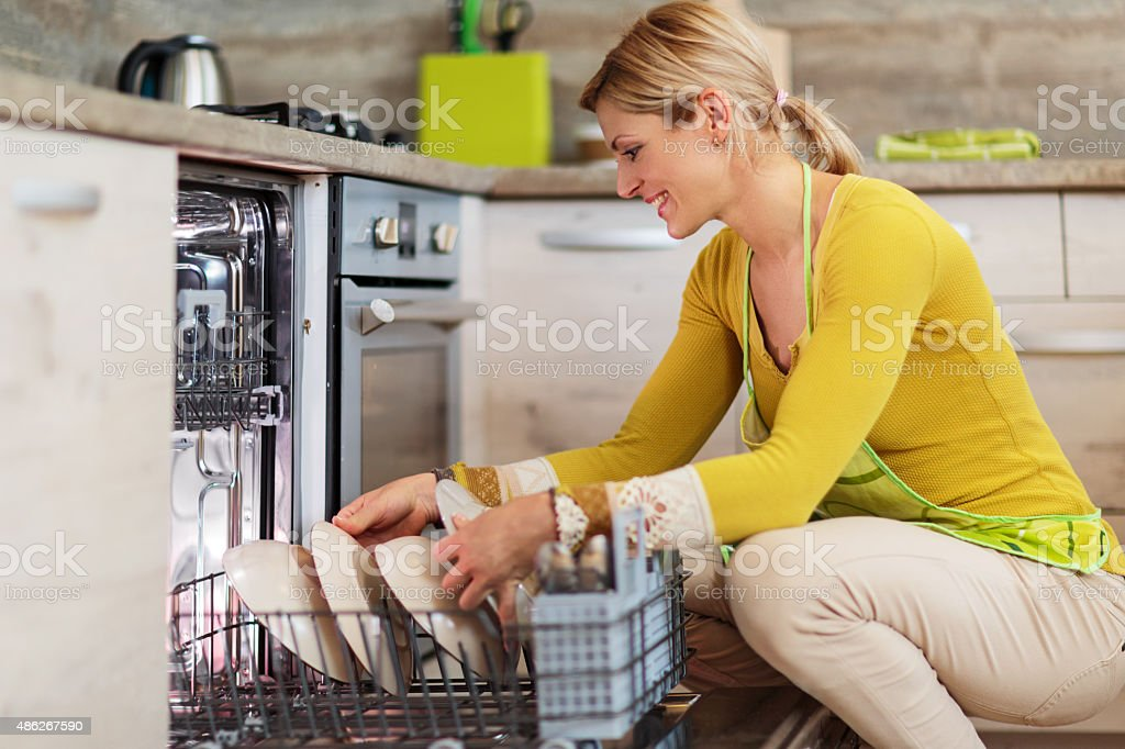 Smiling woman using dishwasher in the kitchen. stock photo