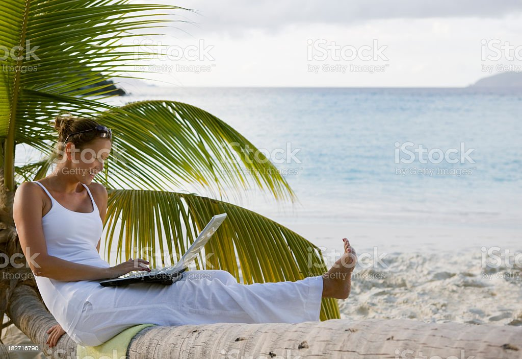 smiling woman using laptop on tropical beach royalty-free stock photo