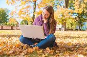 Smiling Woman Using Laptop Sitting on Ground Alone