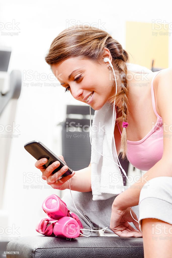 Smiling woman using smart phone at the gym stock photo
