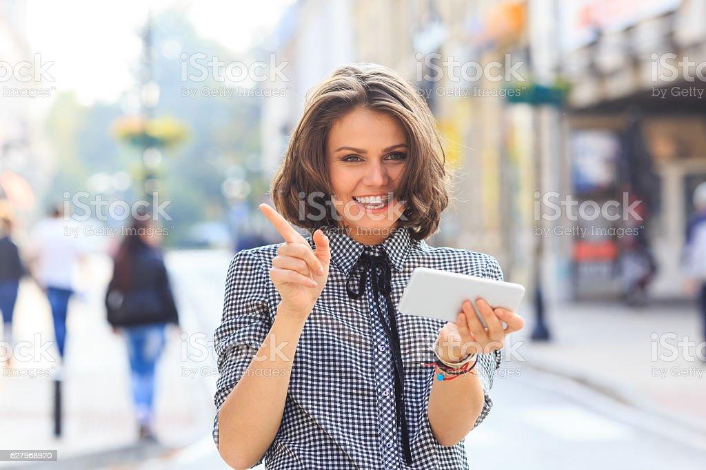 Smiling woman using smart phone on street stock photo
