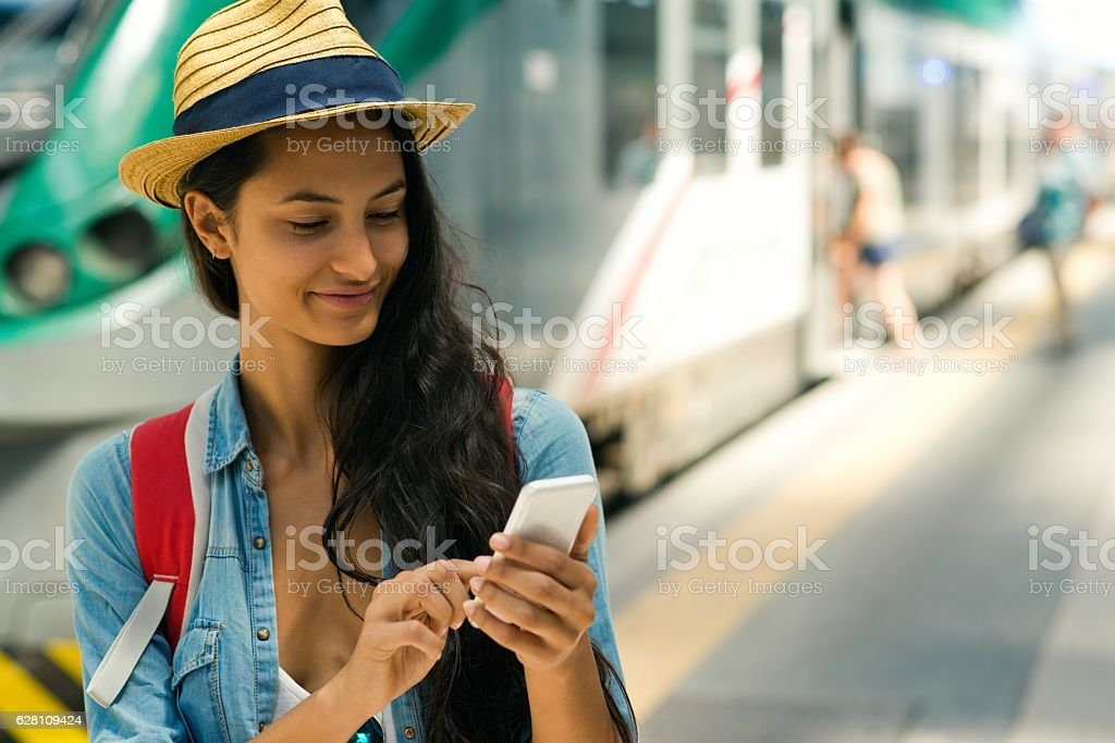 Smiling woman using smartphone at the subway station. stock photo