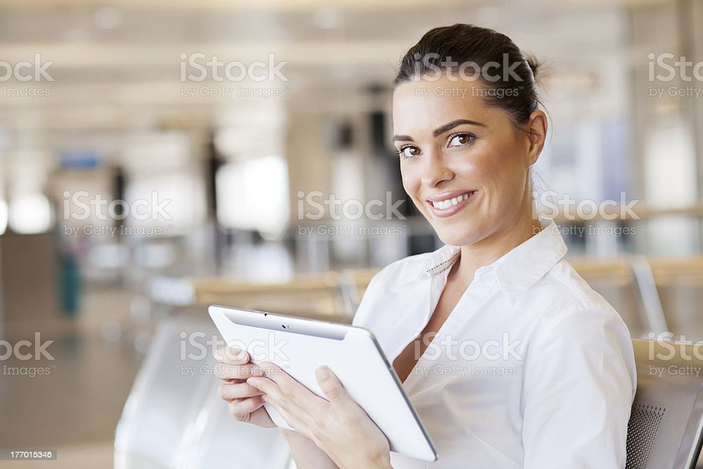 Smiling woman using tablet computer at airport royalty-free stock photo