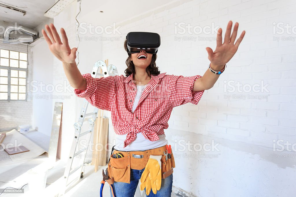 Smiling woman using virtual reality simulator on construction site stock photo