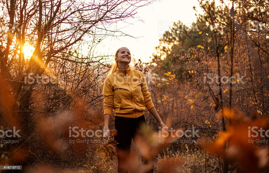 Smiling woman walking in the autumn forest at sunset. stock photo