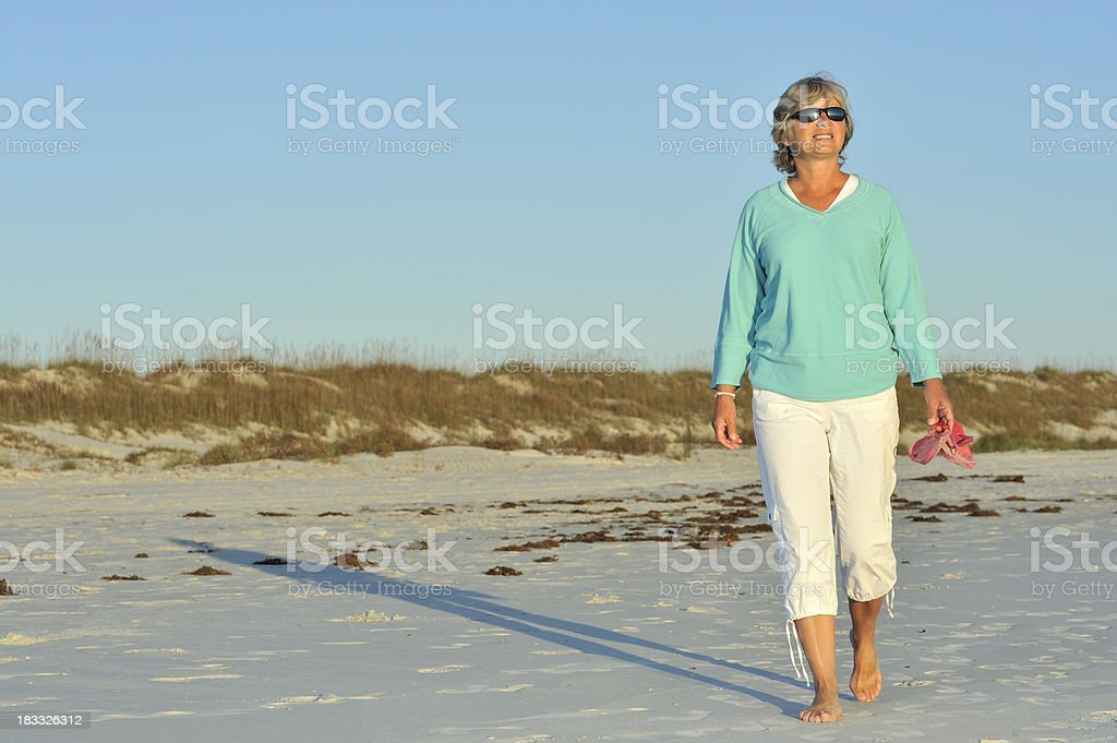 Smiling woman walking on beach in the morning, south vacation royalty-free stock photo
