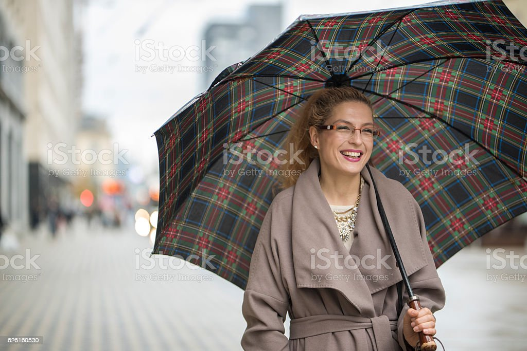 Smiling woman walking on the street stock photo