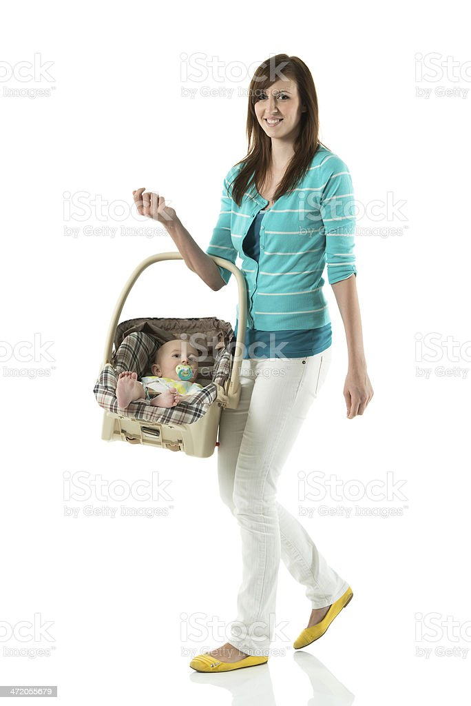Smiling woman walking with baby in carrier stock photo