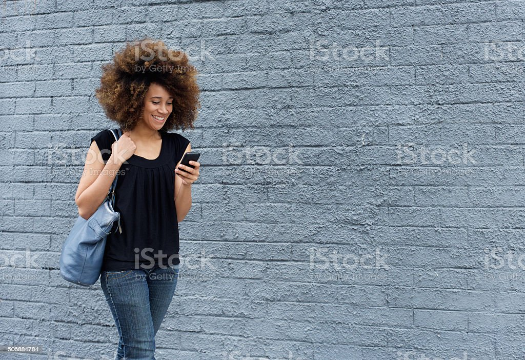 Smiling woman walking with cell phone stock photo