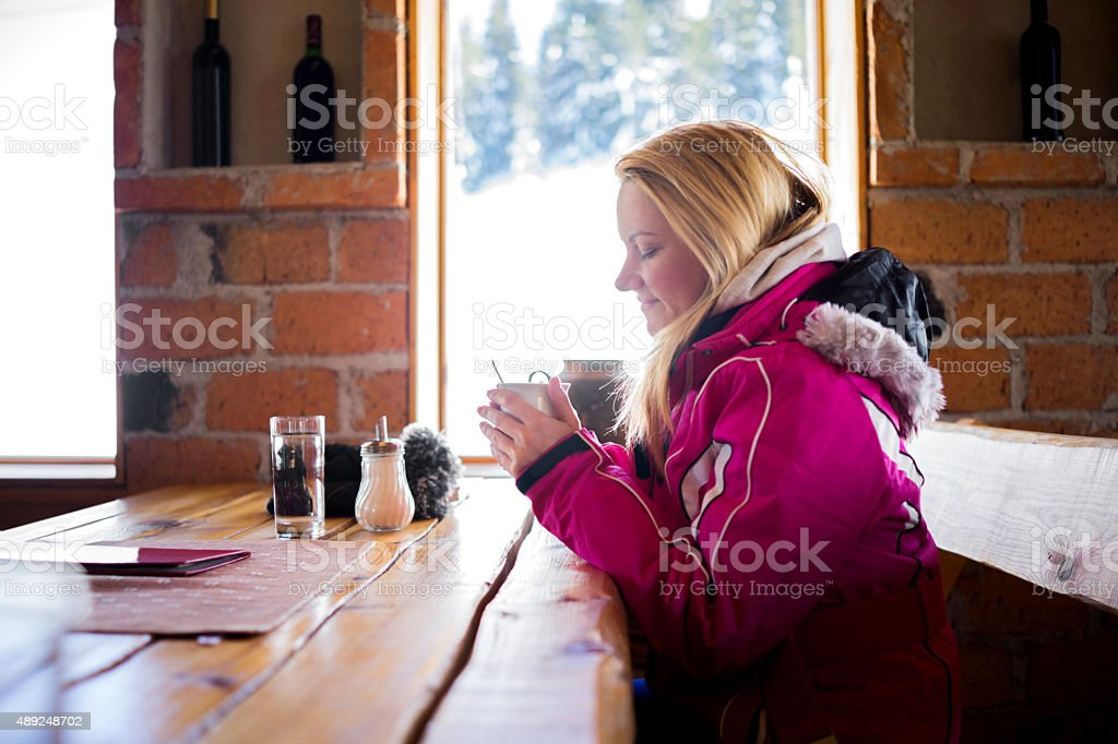 Smiling woman warming with a cup of hot tea. stock photo