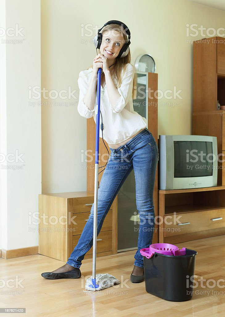 Smiling woman washes the floor with mop stock photo