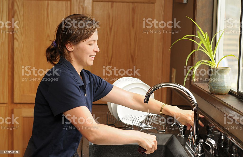 Smiling woman washing dishes in a kitchen with wood cabinets royalty-free stock photo