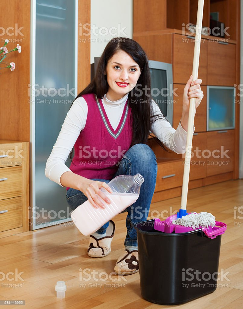 Smiling  woman washing  floor with mop and detergent stock photo