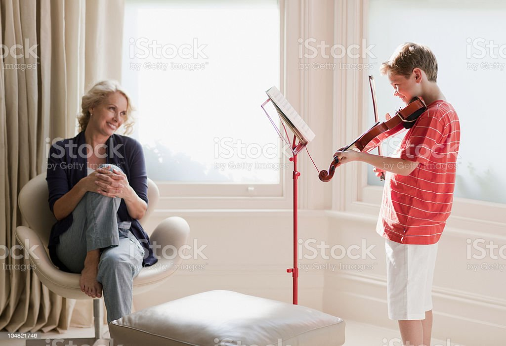 Smiling woman watching boy play violin royalty-free stock photo