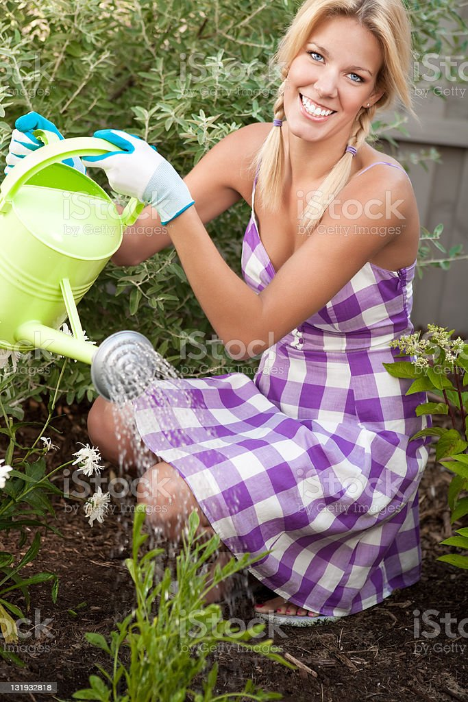 Smiling woman watering the garden royalty-free stock photo