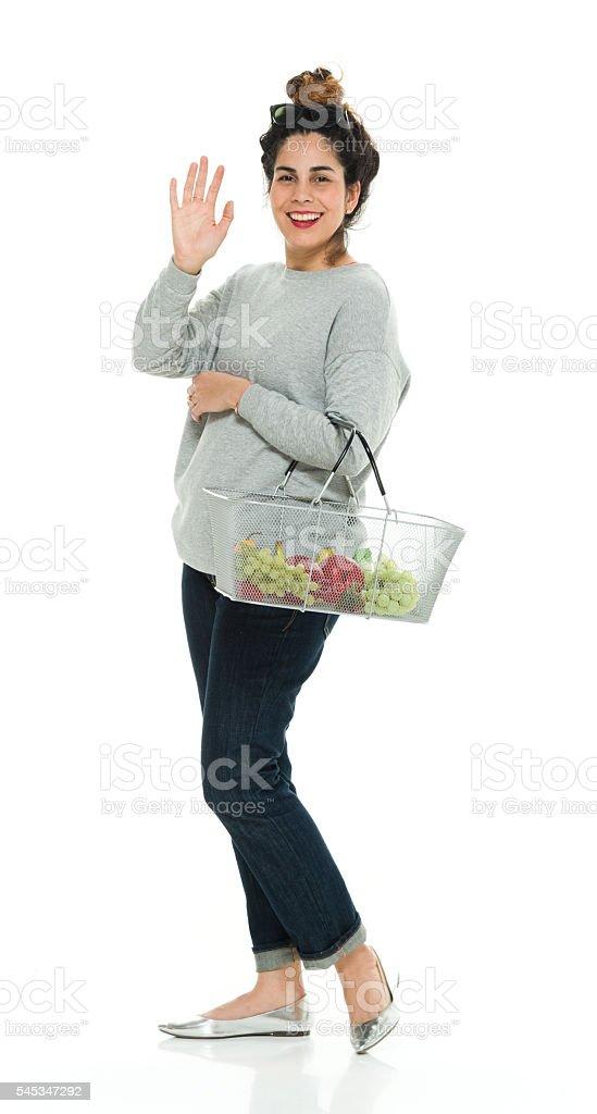 Smiling woman waving hand stock photo
