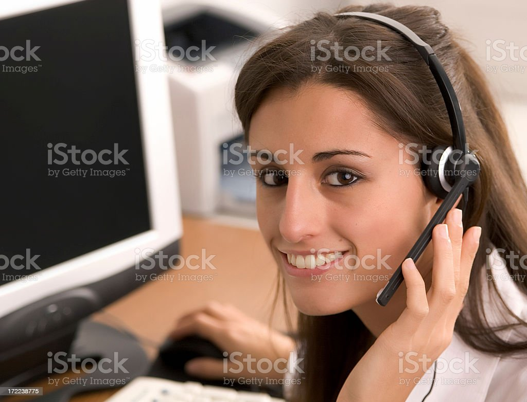 Smiling woman wearing headset in front of computer monitor royalty-free stock photo
