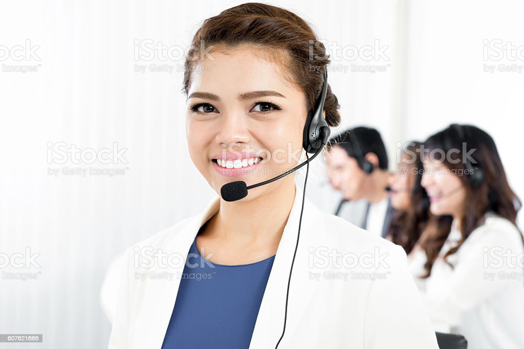 Smiling woman wearing microphone headset in call center stock photo